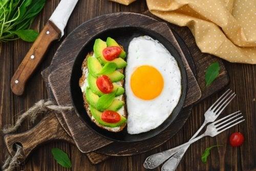 Uovo fritto in padella con pane avocado e pomodorini