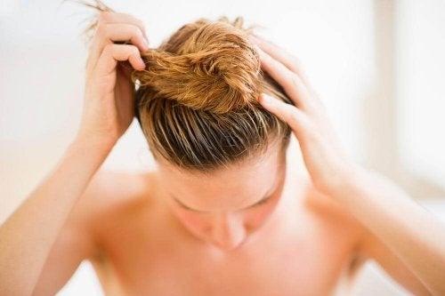 Ragazza bionda raccoglie sulla testa i capelli bagnati