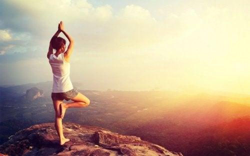Donna pratica lo yoga sulla cima di una collina