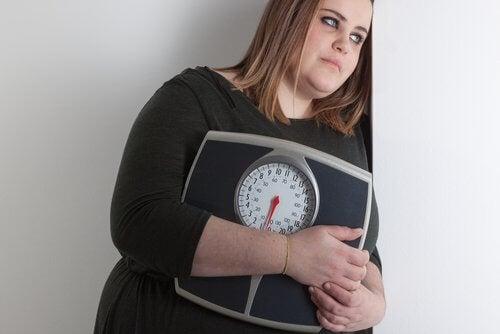 Ragazza in sovrappeso tiene una bilancia tra le braccia