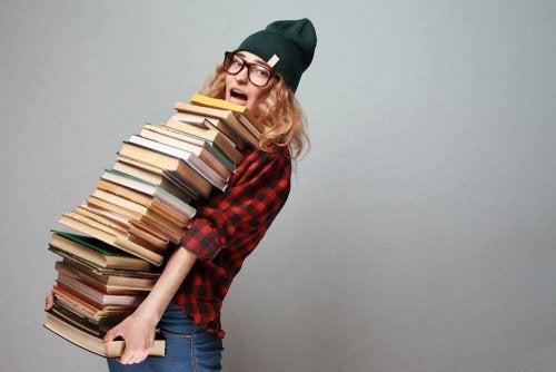 Ragazza tiene tra le braccia una pila di libri