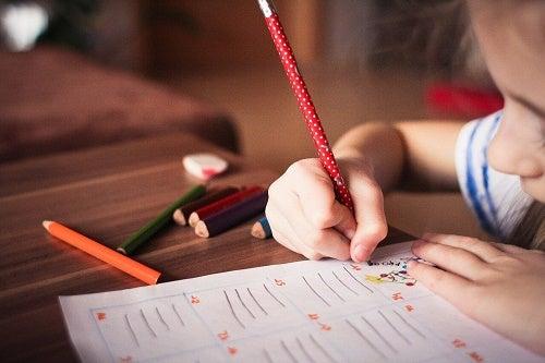 Mano di bambino che scrive su foglio