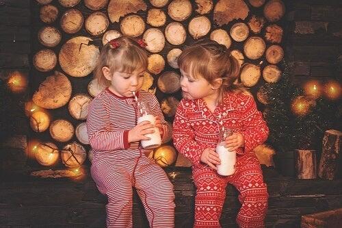 Due bimbe piccole bevono latte sedute davanti alla legna