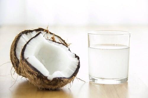 Due cocchi con bicchiere di acqua di cocco