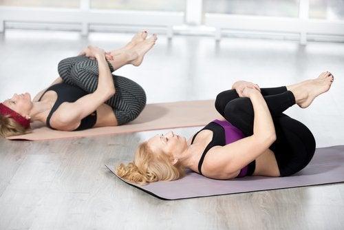 Due donne con ginocchia al petto sdraiate su tappetini