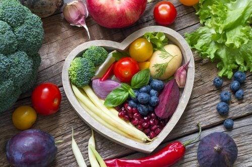 Un recipiente a cuore con frutti e verdure dentro