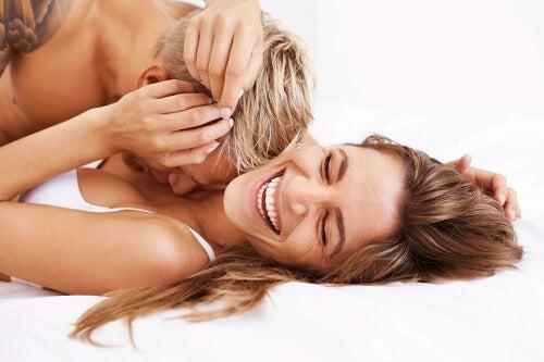 Ragazza sorride su letto baciata da fidanzato