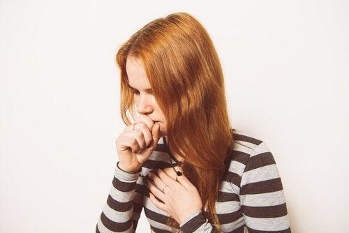 Bambina con i capelli rossi mentre tossisce