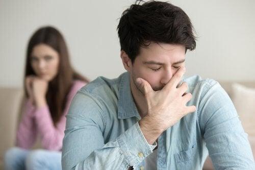 Ragazzo piange mentre ragazza triste lo guarda da dietro