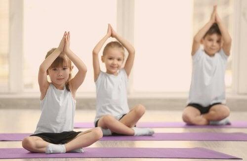 Tre bambini fanno yoga con le mani in alto