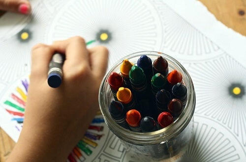 Mano di bambino che disegna accanto a portapenne con pastelli colorati