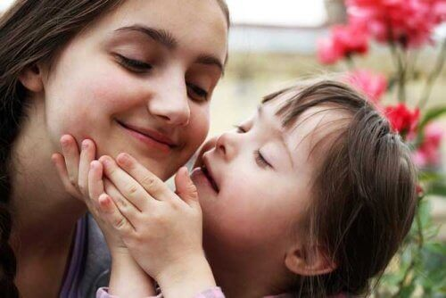Bambina down che dà un bacio alla mamma.