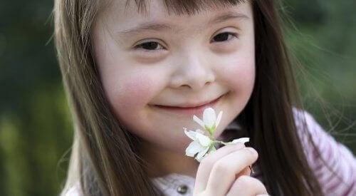 Bambina down tiene fiorellino in mano davanti alla bocca.