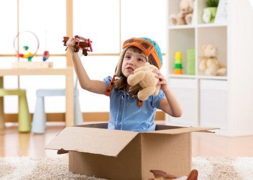 Bambino dentro uno scatolone gioca a fare l'aviatore