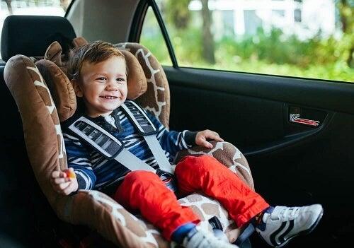 Bimbo sorridente seduto in seggiolino auto