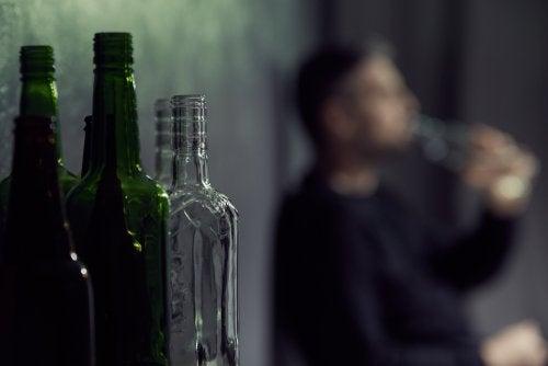 Bottiglie di vetro e in fondo uomo beve alchol