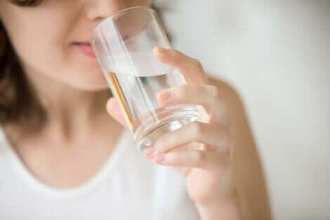 Donna che beve un bicchiere d'acqua.