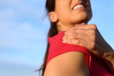 Donna con dolore alla spalla