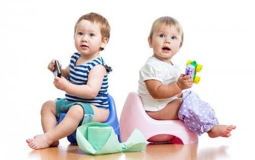 Due bambini seduti sul vasino