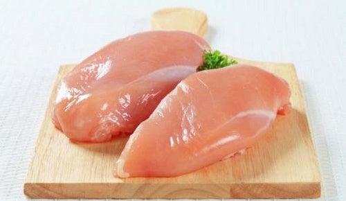 Due petti di pollo su tagliere di legno