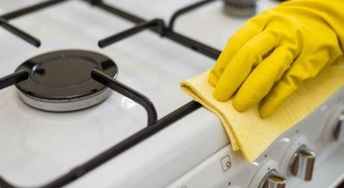 Mano con guanti e spugnetta pulisce i fornelli