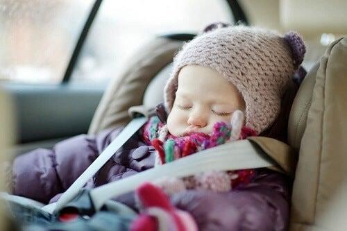 Neonata con cappello e giubbotto dorme in seggiolino auto