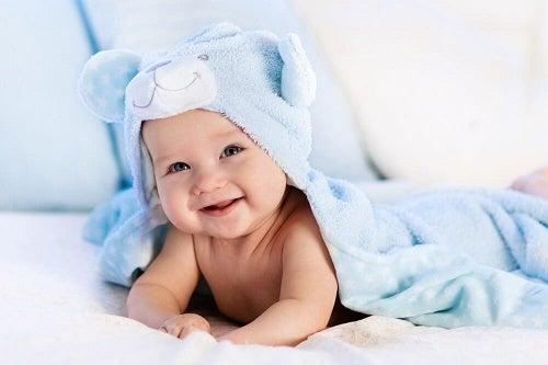 Neonato sorride con pigiama di peluche in testa