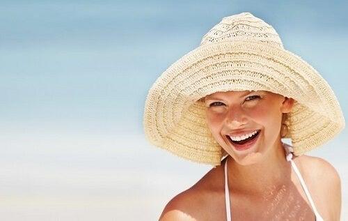 Ragazza bionda con cappello sorride in spiaggia
