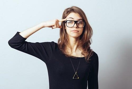 Ragazza con occhiali con dito su fronte