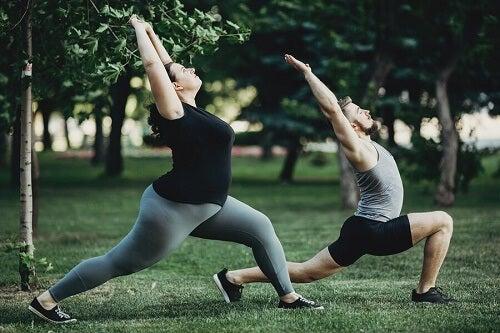 Ragazza obesa e ragazza fanno yoga al parco