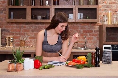 Ragazza scrive su tavola con prodotti naturali