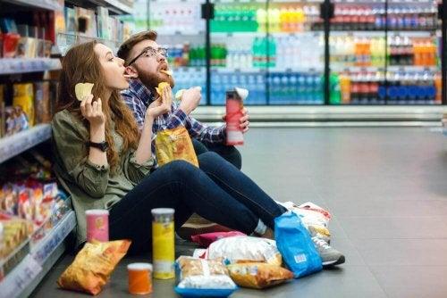 Ragazzi al supermercato mangiano patatine seduti per terra