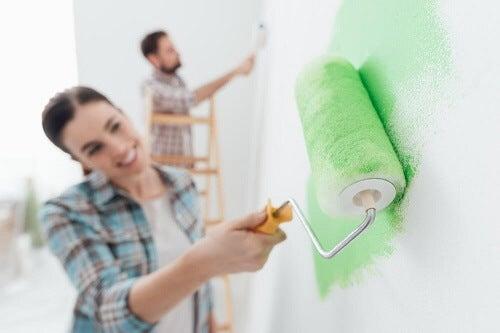 Ragazzo e ragazza dipingono assieme parete