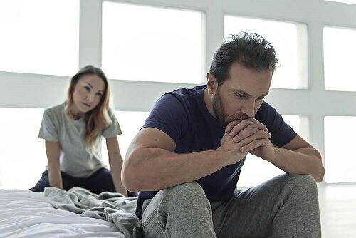 Ragazzo su letto arrabiato con donna dietro