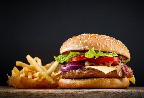 Un hamburger di pollo in panino con patate fritta e lato