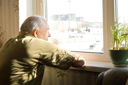 Uomo anziano guarda attraverso finestra chiusa