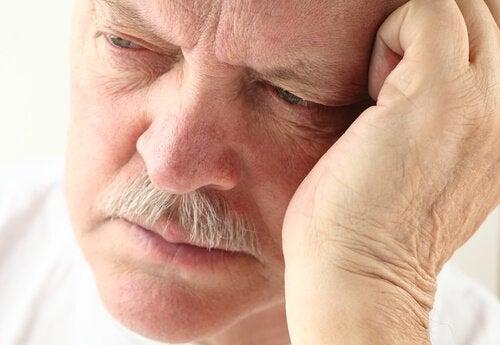 Anziano pensieroso con mano su fronte