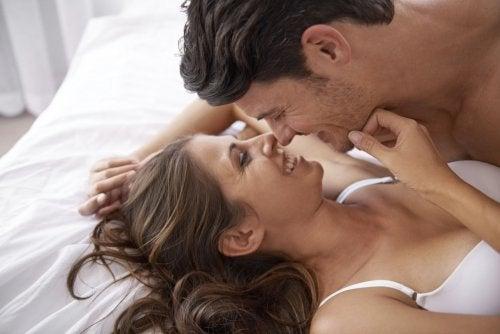 Uomo e donna vicini su letto scherzano