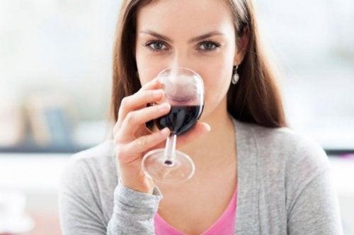 Donna che beve un bicchiere di vino rosso