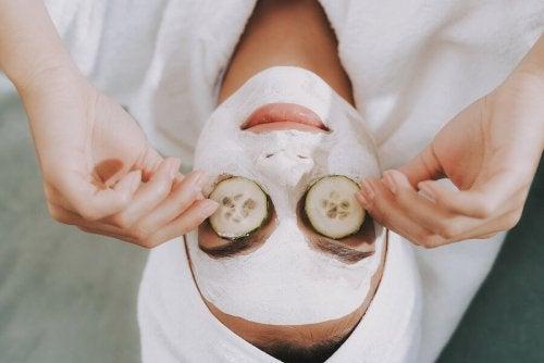 Donna con fettine di cetriolo sugli occhi