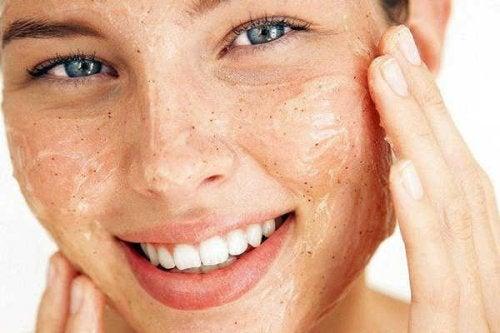 Ragazza esfolia il viso per avere una pelle morbida e pulita