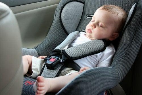 Bambino che dorme nel seggiolino affrontare un lungo viaggio con un neonato