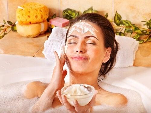 Donna nella vasca applica una maschera per il viso