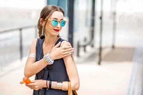 Donna che cammina per la città spalmandosi crema solare