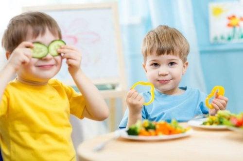Bambini giocano a tavola mentre mangiano le verdure