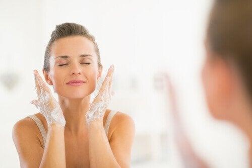 Donna deterge il viso davanti allo specchio