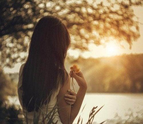 Donna di spalle con fiore in mano