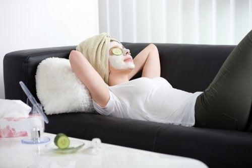 Donna distesa sul divano con maschera e fettine di cetriolo