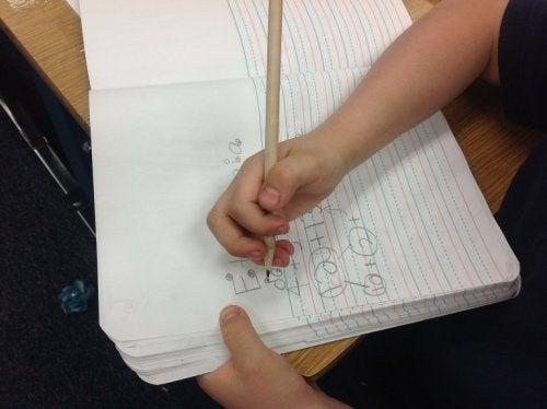 Bambino scrive su quaderno a righe
