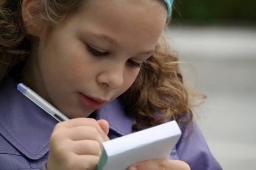 Bambina che scrive su di un block notes esercizi di ortografia